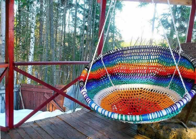 Плетеное кресло подвешенное на террасе
